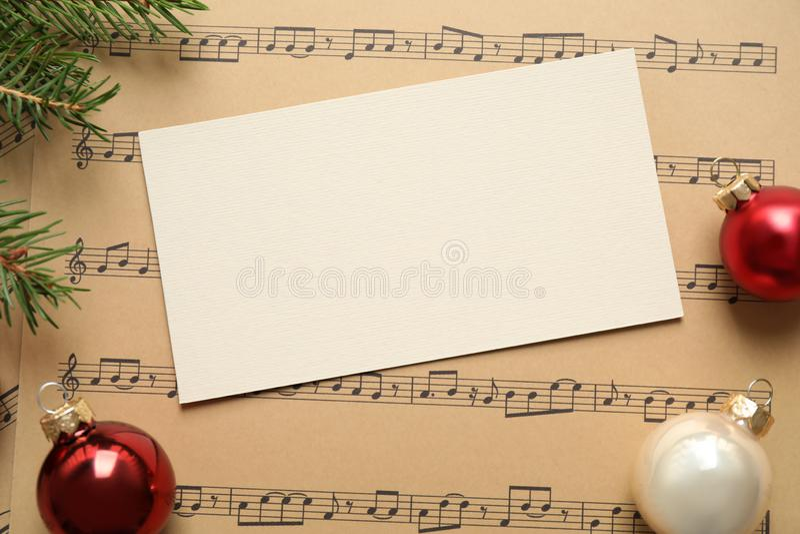 Επίπεδη σύνθεση με χριστουγεννιάτικες διακοσμήσεις και λευκή κάρτα σε μουσικά φύλλα στοκ φωτογραφία