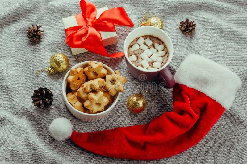 επίπεδος βάλτε διαμορφωμένα τα αστέρι μπισκότα, την καυτή σοκολάτα, το κιβώτιο δώρων και το κόκκινο καπέλο Άγιου Βασίλη στοκ φωτογραφία με δικαίωμα ελεύθερης χρήσης