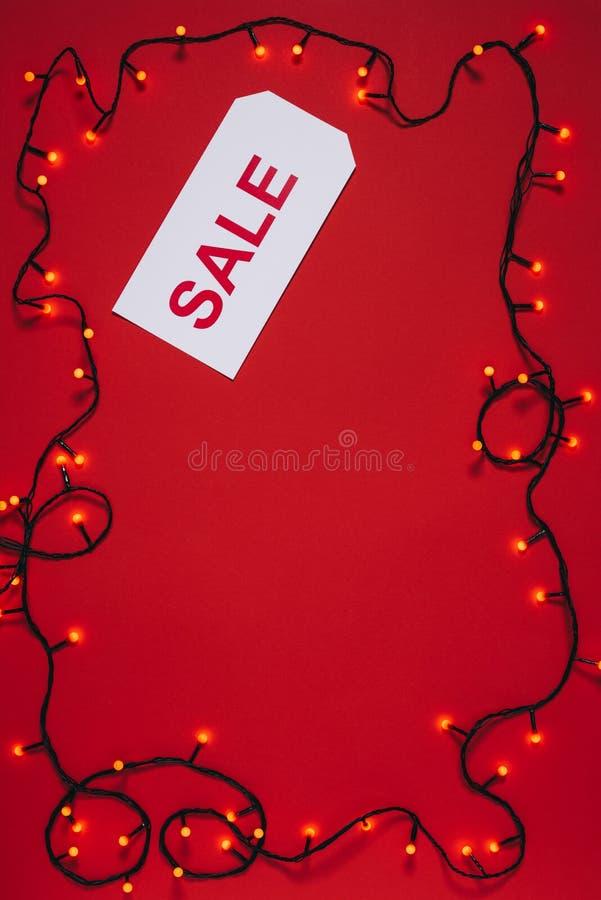 επίπεδος βάλτε με τη τιμή με τα φω'τα εγγραφής και Χριστουγέννων πώλησης που απομονώνονται στο κόκκινο στοκ εικόνες