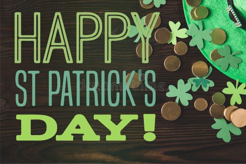Επίπεδος βάλτε με το πράσινα καπέλο, τα νομίσματα και τα τριφύλλια στην ξύλινη επιφάνεια με την ευτυχή ημέρα του ST patricks στοκ φωτογραφία με δικαίωμα ελεύθερης χρήσης