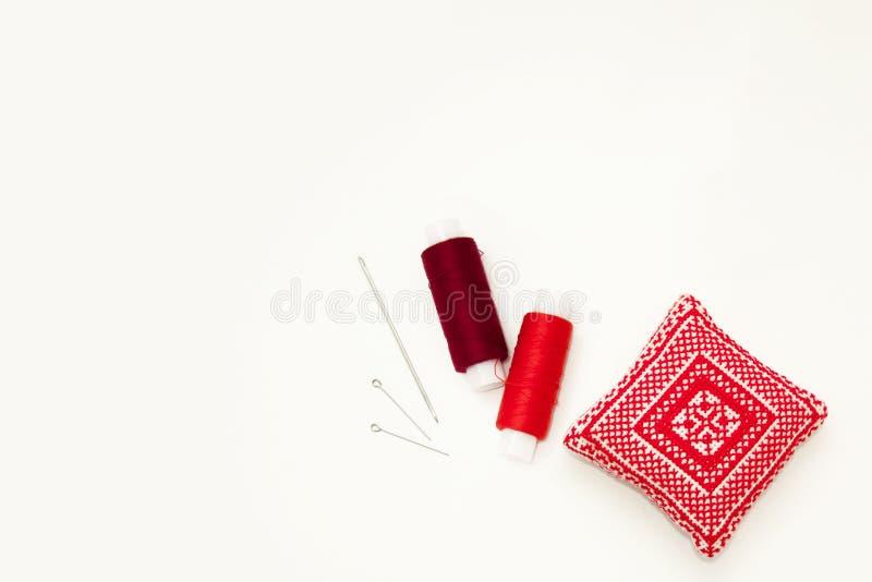 Επίπεδος βάλτε με το χειροποίητο κόκκινο κεντημένο μαξιλάρι βελόνων, στροφία νημάτων, καρφίτσες, βελόνες, χλεύη επάνω, τοπ άποψη  στοκ εικόνες