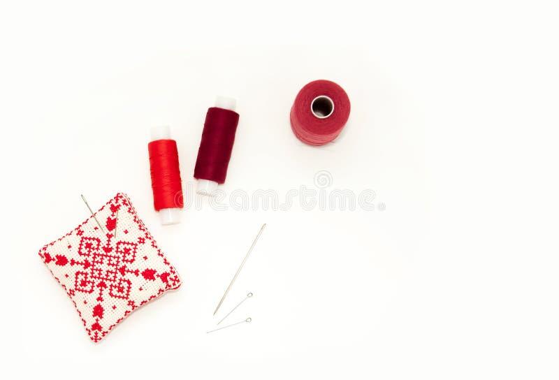 Επίπεδος βάλτε με το χειροποίητο κόκκινο κεντημένο μαξιλάρι βελόνων, στροφία νημάτων, καρφίτσες, βελόνες, χλεύη επάνω, τοπ άποψη  στοκ εικόνα