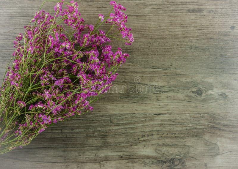 Επίπεδος βάλτε τα λουλούδια στο ξύλινο υπόβαθρο στοκ φωτογραφία