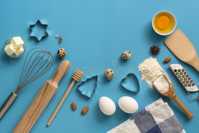 Επίπεδος βάλτε τα συστατικά για τα εργαλεία ψησίματος και κουζινών σε ένα μπλε υπόβαθρο Τοπ άποψη, θέση για το κείμενό σας στοκ φωτογραφία με δικαίωμα ελεύθερης χρήσης