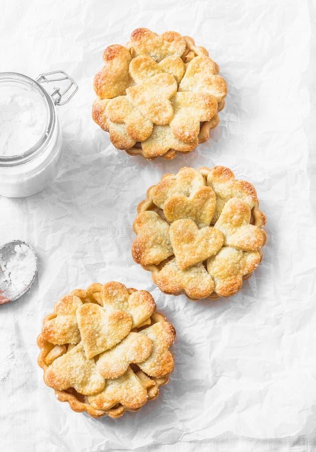 Επίπεδος βάλτε τα τριζάτα tartlets μήλων ζύμης shortcrust στο ελαφρύ υπόβαθρο, τοπ άποψη Ψήσιμο ημέρας βαλεντίνων ` s στοκ φωτογραφίες