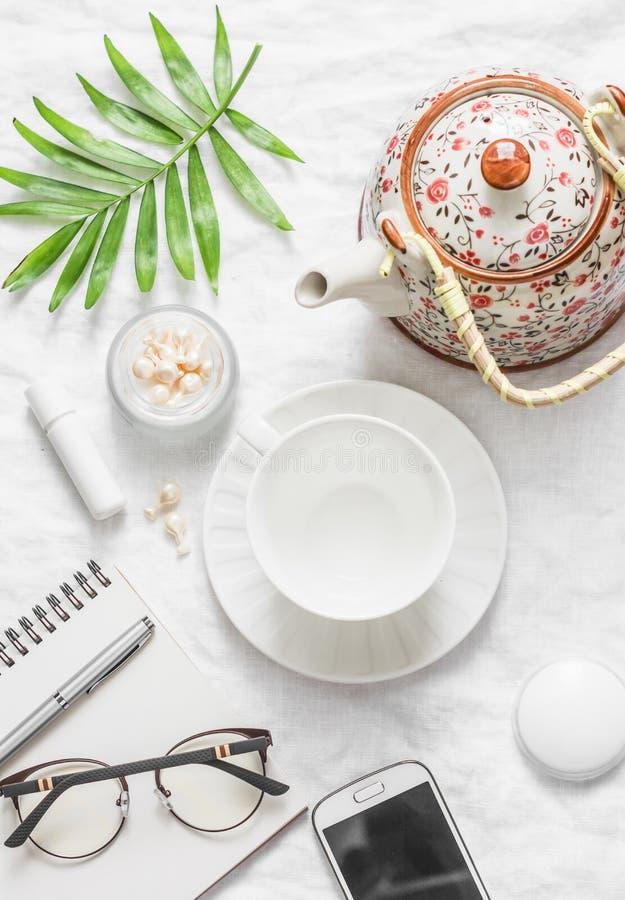 Επίπεδος βάλτε την άνετη έμπνευση πρωινού προγραμματίζοντας το θηλυκό πίνακα - teapot, φλυτζάνι τσαγιού, σημειωματάριο, γυαλιά, τ στοκ φωτογραφίες με δικαίωμα ελεύθερης χρήσης