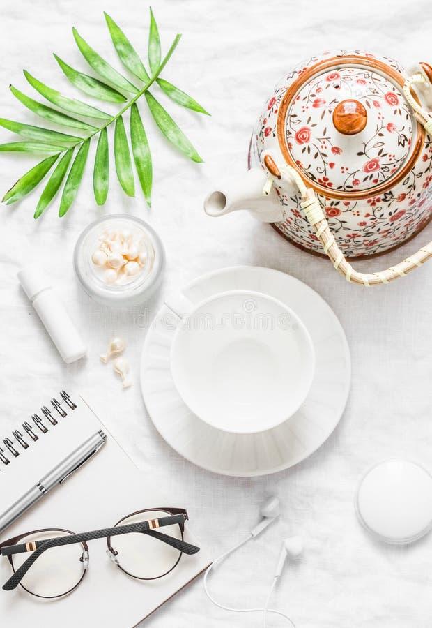 Επίπεδος βάλτε την άνετη έμπνευση πρωινού προγραμματίζοντας το θηλυκό πίνακα - teapot, φλυτζάνι τσαγιού, σημειωματάριο, γυαλιά, κ στοκ φωτογραφία