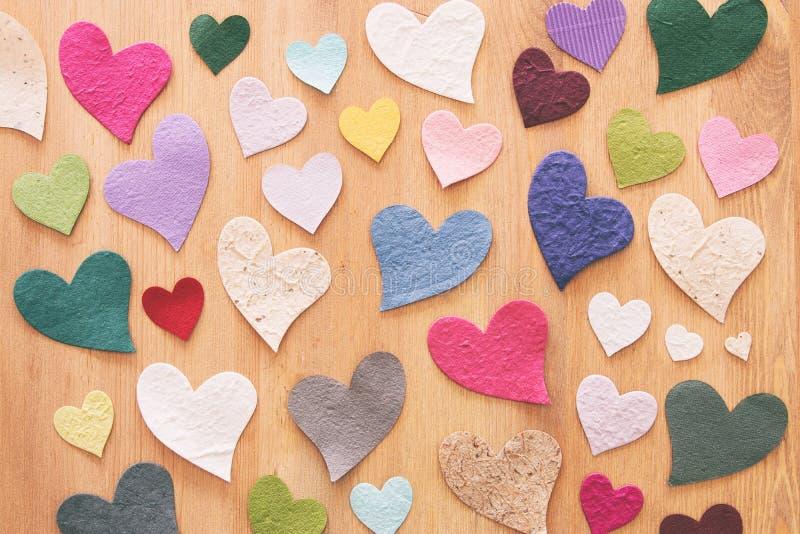 Επίπεδος βάλτε την εικόνα πολλών ζωηρόχρωμων καρδιών πέρα από το ξύλινο υπόβαθρο στοκ φωτογραφίες