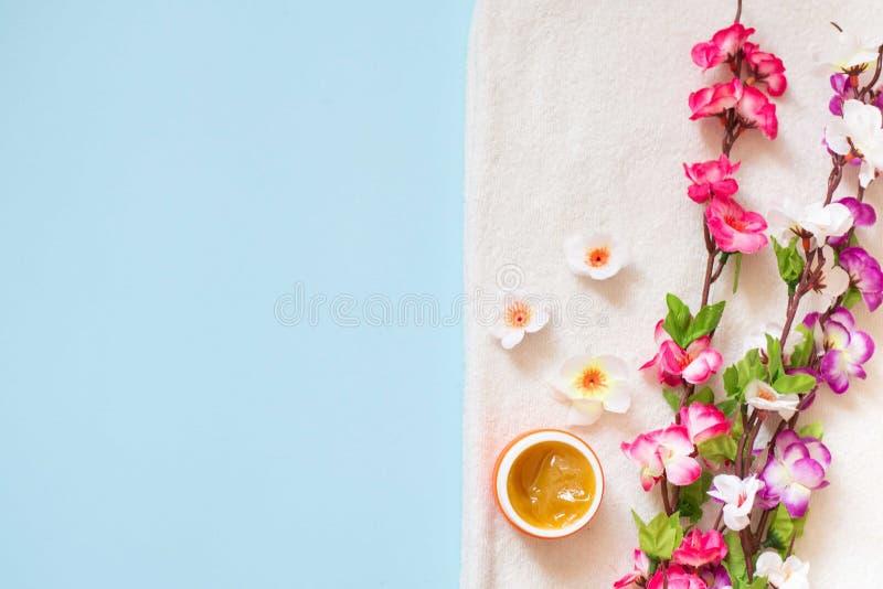 Επίπεδος βάλτε της κρέμας SPA και χρωματίστε τα λουλούδια στην άσπρη πε στοκ φωτογραφίες με δικαίωμα ελεύθερης χρήσης