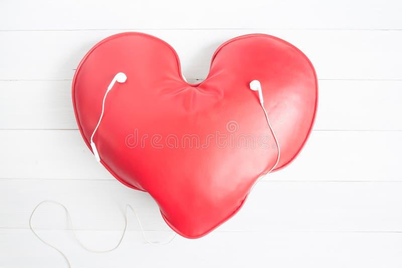 Επίπεδος βάλτε της κόκκινης καρδιάς με τα ακουστικά, ημέρα βαλεντίνων και αγαπήστε ομο στοκ φωτογραφίες