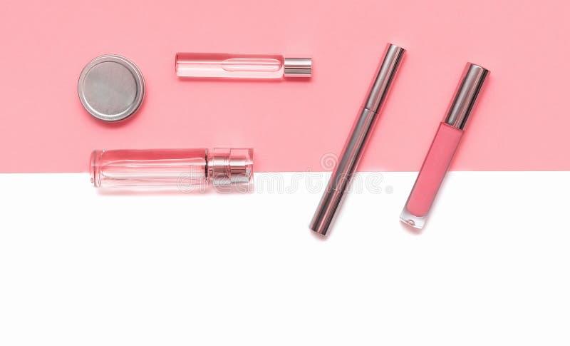 Επίπεδος βάλτε τη σύνθεση με τα διακοσμητικά προϊόντα makeup και parfume στο κοράλλι και το απομονωμένο άσπρο υπόβαθρο Makeup και στοκ εικόνα