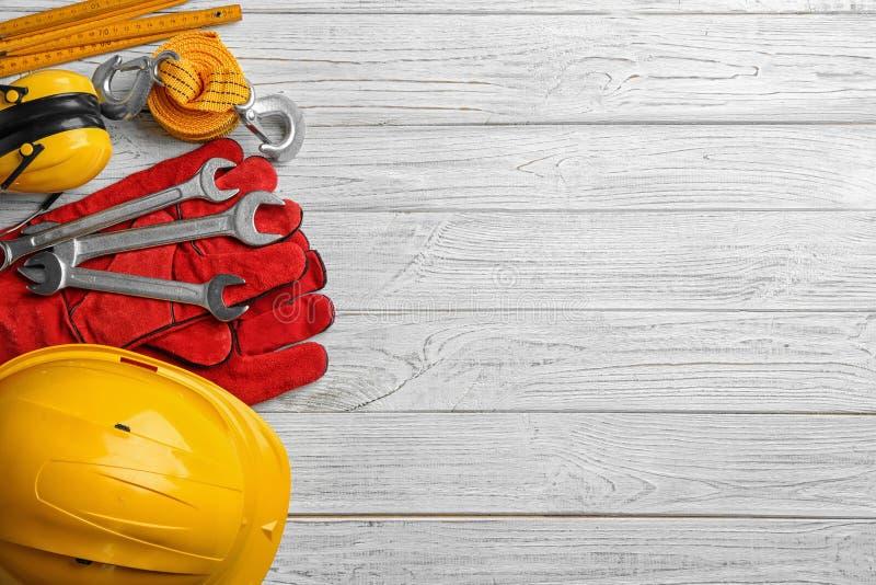 Επίπεδος βάλτε τη σύνθεση με τα διαφορετικά εργαλεία κατασκευής και το διάστημα για το κείμενο στο ξύλινο υπόβαθρο στοκ φωτογραφία με δικαίωμα ελεύθερης χρήσης