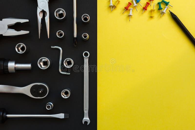 Επίπεδος βάλτε τη σύνθεση με τα διαφορετικά εργαλεία κατασκευής στο μαύρο και κίτρινο υπόβαθρο Τοπ άποψη των εργαλείων πινάκων ελ στοκ εικόνες