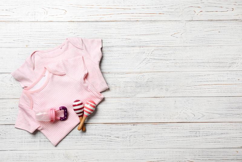 Επίπεδος βάλτε τη σύνθεση με τα ενδύματα και τα εξαρτήματα μωρών στο ξύλινο υπόβαθρο στοκ εικόνες
