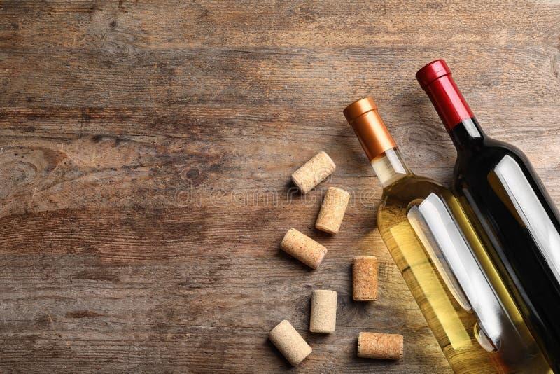Επίπεδος βάλτε τη σύνθεση με τα μπουκάλια του κρασιού και βουλώνει στον ξύλινο πίνακα E στοκ εικόνα