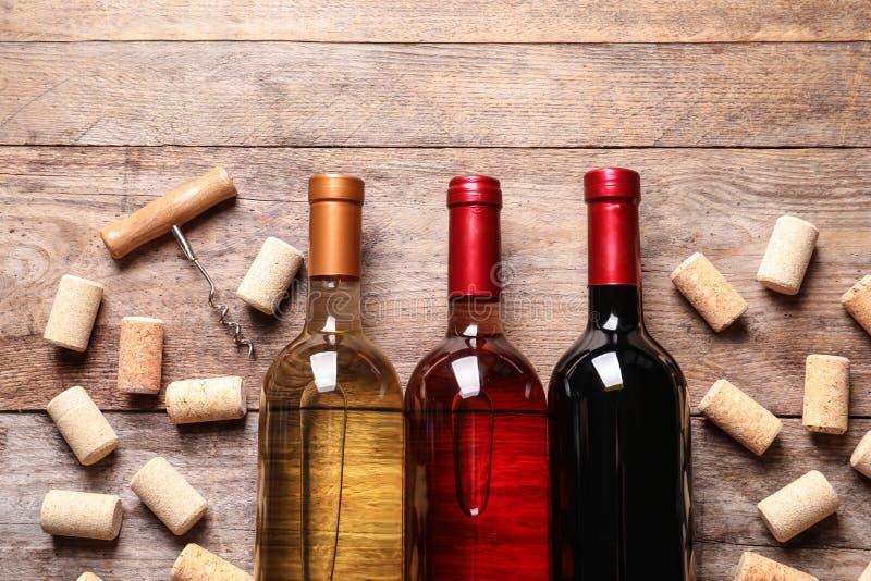 Επίπεδος βάλτε τη σύνθεση με τα μπουκάλια του κρασιού και βουλώνει επάνω στοκ εικόνες
