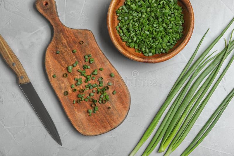 Επίπεδος βάλτε τη σύνθεση με τα πράσινα κρεμμύδια, το μαχαίρι και το κύπελλο στοκ εικόνες