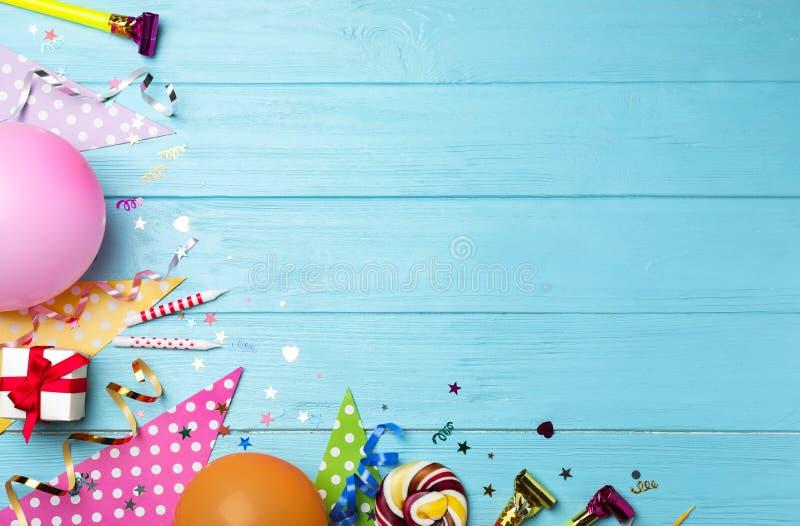 Επίπεδος βάλτε τη σύνθεση με τα στοιχεία γιορτών γενεθλίων στο μπλε ξύλινο υπόβαθρο στοκ εικόνες