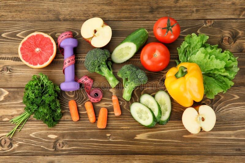 Επίπεδος βάλτε τη σύνθεση με τα φρέσκα λαχανικά, τα φρούτα και τον αλτήρα στο ξύλινο υπόβαθρο o στοκ εικόνες