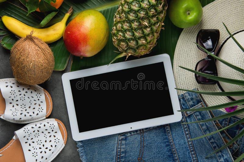 Επίπεδος βάλτε τη σύνθεση με την τροπική καρύδα μπανανών μάγκο ανανά φρούτων στο μεγάλο φύλλο φοινικών Καπέλο παντοφλών σορτς τζι στοκ εικόνα με δικαίωμα ελεύθερης χρήσης