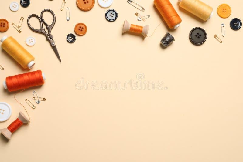 Επίπεδος βάλτε τη σύνθεση με το ψαλίδι και άλλα ράβοντας εξαρτήματα στο ανοικτό κίτρινο υπόβαθρο, διάστημα για απεικόνιση αποθεμάτων