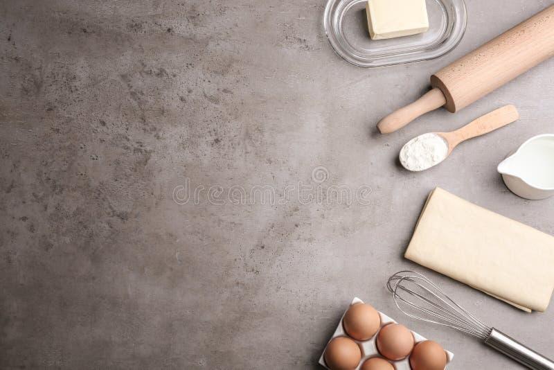 Επίπεδος βάλτε τη σύνθεση με τη φρέσκια ζύμη στον γκρίζο πίνακα Ζύμη ριπών στοκ φωτογραφίες
