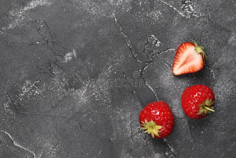 Επίπεδος βάλτε τη σύνθεση τριών ώριμων φραουλών σε ένα σκοτεινό υπόβαθρο στοκ εικόνα