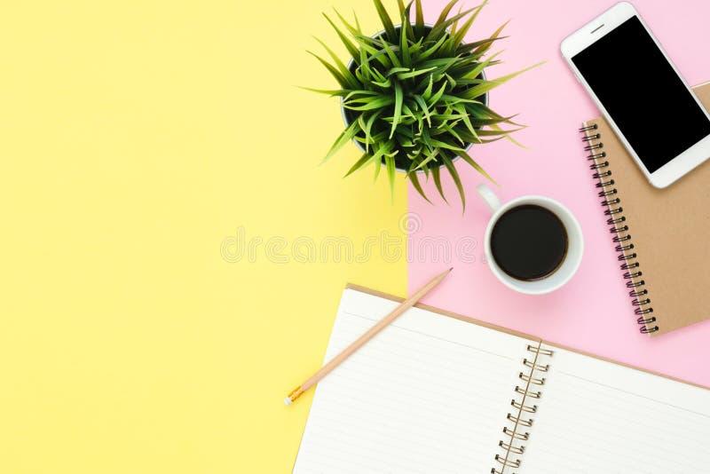Επίπεδος βάλτε τη τοπ άποψη ενός χώρου εργασίας με την άσπρη κενή σελίδα σημειωματάριων, το φλυτζάνι καφέ και τη χλεύη επάνω στο  στοκ φωτογραφία με δικαίωμα ελεύθερης χρήσης