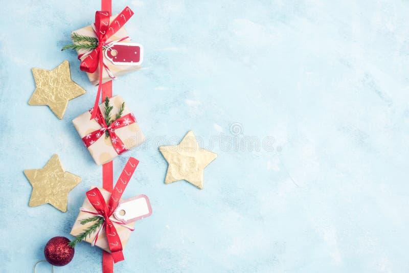 Επίπεδος βάλτε τη τοπ άποψη τρία δώρα Χριστουγέννων και χρυσά αστέρια στο μπλε διανυσματική απεικόνιση