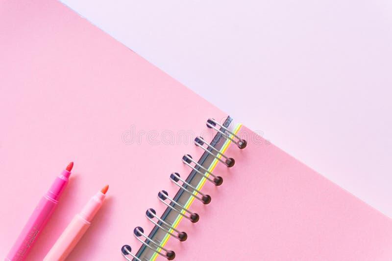 Επίπεδος βάλτε του σημειωματάριου στο ρόδινο υπόβαθρο χρώματος κρητιδογραφιών, ελάχιστο ύφος Διάστημα εργασίας στοκ εικόνα