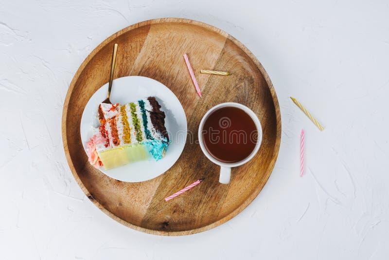 Επίπεδος βάλτε του vegan κομματιού κέικ ουράνιων τόξων στον ξύλινο δίσκο με τα κεριά γενεθλίων στοκ φωτογραφία με δικαίωμα ελεύθερης χρήσης