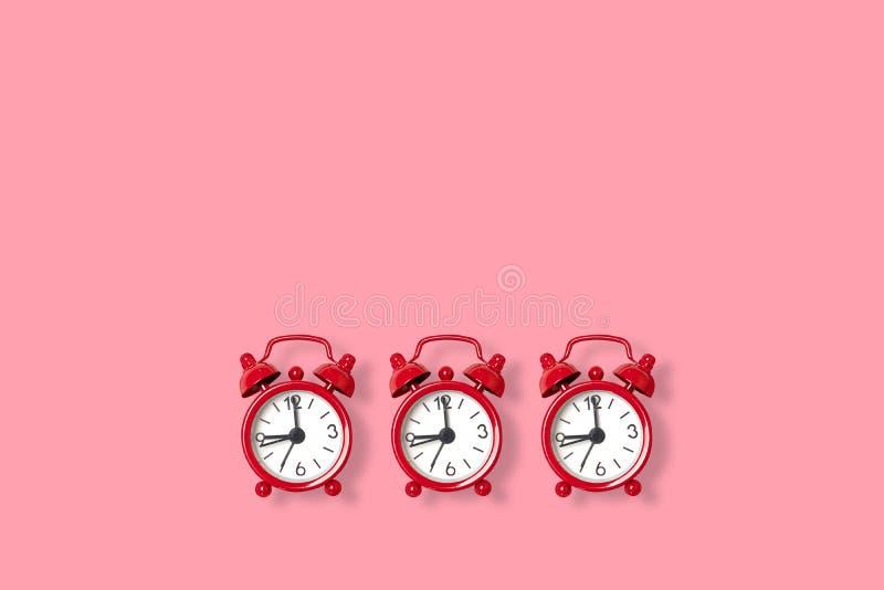 Επίπεδος βάλτε το αναδρομικό όμορφο νέο ξυπνητήρι σε ένα ρόδινο υπόβαθρο r διανυσματική απεικόνιση