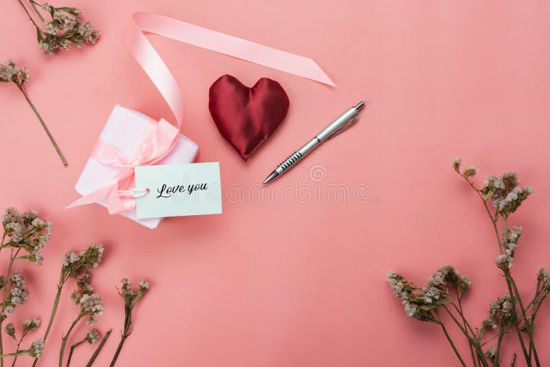 Επίπεδος βάλτε το δώρο με την καρδιά και το λουλούδι στη σύγχρονη ρόδινη ταπετσαρία grunge στοκ εικόνα