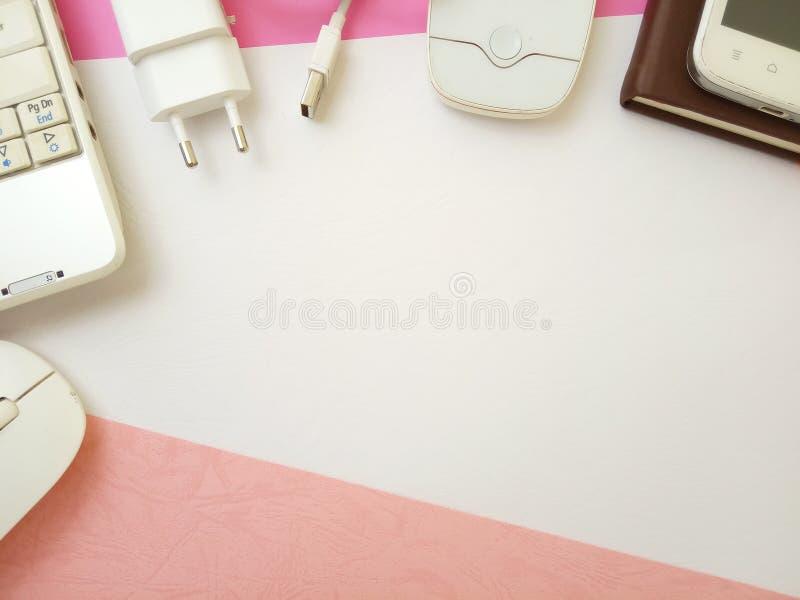 Επίπεδος βάλτε, το εννοιολογικό επίπεδο γραφείων βάζει το σημειωματάριο και το ασύρματο ποντίκι στο texturized ρόδινο άσπρο υπόβα στοκ εικόνα