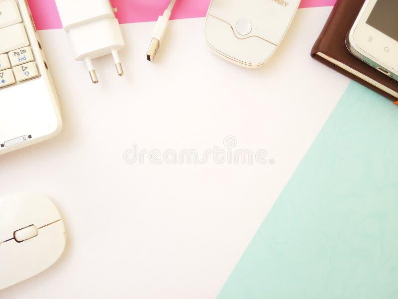 Επίπεδος βάλτε, το εννοιολογικό επίπεδο γραφείων βάζει το σημειωματάριο και το ασύρματο ποντίκι στο texturized ρόδινο άσπρο υπόβα στοκ φωτογραφία με δικαίωμα ελεύθερης χρήσης