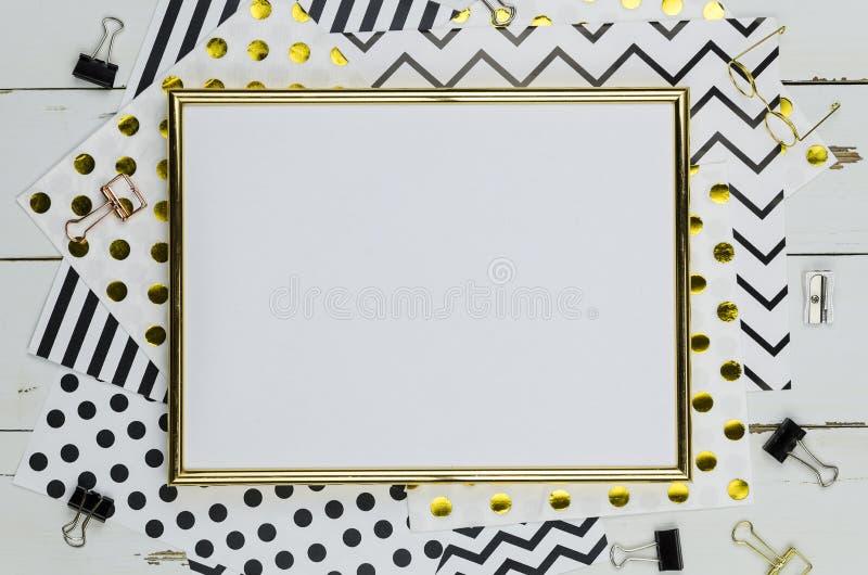Επίπεδος βάλτε το πρότυπο με το χρυσό πλαίσιο, και τις προμήθειες γραφείων στο άσπρο ξύλινο υπόβαθρο Τοπ πρότυπο άποψης στοκ εικόνες