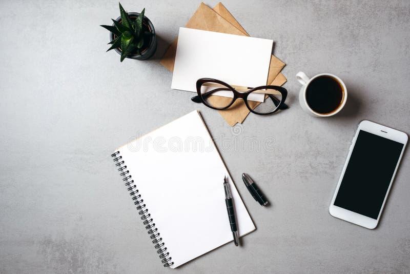 Επίπεδος βάλτε το σύγχρονο ελάχιστο γραφείο εγχώριου χώρου εργασίας με το κενό σημειωματάριο, γυαλιά, smartphone, succulent εγκατ στοκ εικόνες