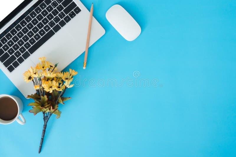 Επίπεδος βάλτε το τοπ διάστημα αντιγράφων άποψης ενός λειτουργώντας γραφείου με το άσπρο lap-top, το φλυτζάνι καφέ, τις προμήθειε στοκ εικόνες