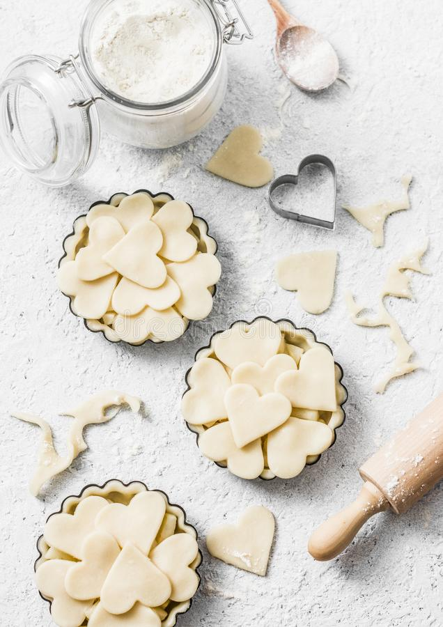 Επίπεδος βάλτε το υπόβαθρο ψησίματος ημέρας βαλεντίνων ` s Ακατέργαστα tartlets μήλων στο πιάτο ψησίματος και συστατικά ψησίματος στοκ εικόνες