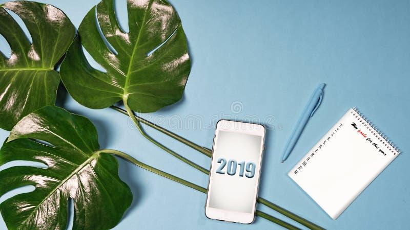 Επίπεδος βάλτε, το 2019, φύλλα Monstera, θέτοντας στόχοι, smartphone στοκ φωτογραφία με δικαίωμα ελεύθερης χρήσης