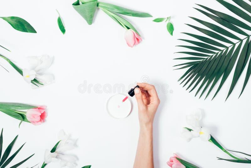Επίπεδος βάλτε το χέρι της γυναίκας που στάζει το καλλυντικό ρευστό στοκ εικόνα με δικαίωμα ελεύθερης χρήσης