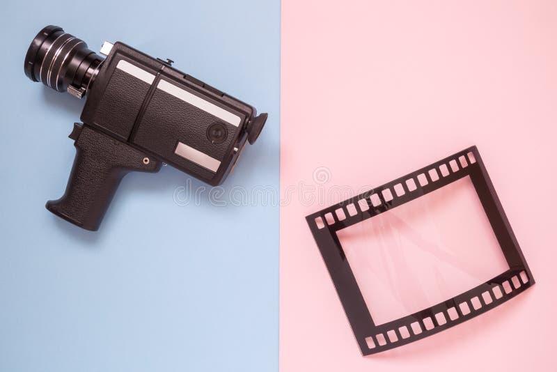 Επίπεδος βάλτε των εκλεκτής ποιότητας βιντεοκάμερων και του κενού πλαισίου με μορφή αναλογικής ταινίας στην πολύχρωμη minimalisti στοκ φωτογραφία με δικαίωμα ελεύθερης χρήσης