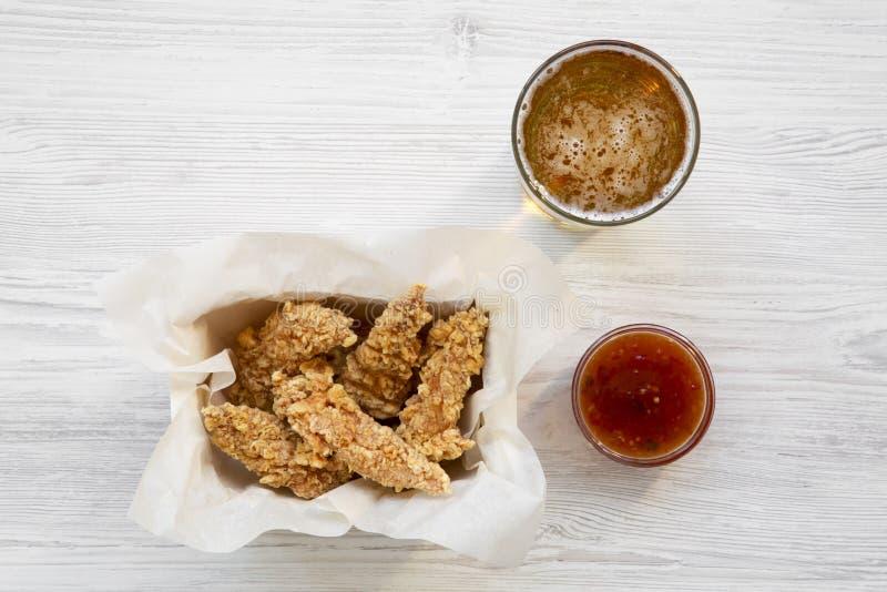 Επίπεδος βάλτε των λουρίδων κοτόπουλου με τη σάλτσα και την κρύα μπύρα σε έναν άσπρο ξύλινο πίνακα υπερυψωμένος στοκ φωτογραφίες