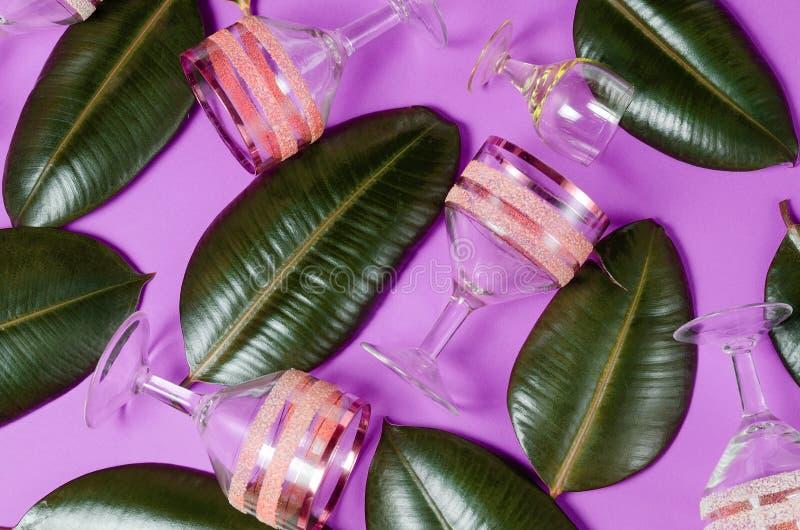 Επίπεδος βάλτε υπεριώδες υπόβαθρο με τα γυαλιά κρασιού και τα πράσινα τροπικά φύλλα στοκ εικόνες με δικαίωμα ελεύθερης χρήσης