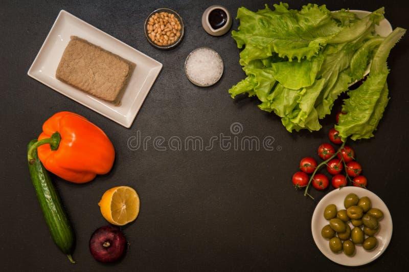 Επίπεδος βάλτε assuage Συστατικά για τη vegan ελληνική σαλάτα στο μαύρο υπόβαθρο διάστημα αντιγράφων στοκ φωτογραφία