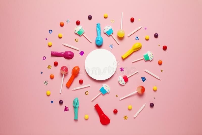 Επίπεδος βάλτε childs τη γιορτή γενεθλίων, ρόδινο σχέδιο υποβάθρου Γλυκές καραμέλες, φωτεινό μπαλόνι, εορταστικά κεριά, cupcake κ στοκ εικόνες