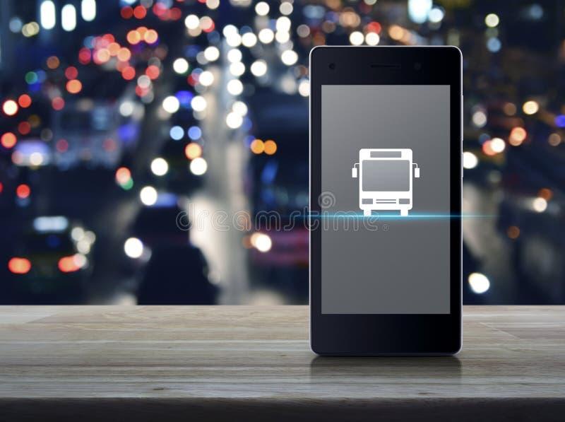 Επίπεδο εικονίδιο λεωφορείων στη σύγχρονη έξυπνη κινητή τηλεφωνική οθόνη στον ξύλινο πίνακα πέρα από ελαφριά πόλη νύχτας θαμπάδων στοκ φωτογραφία με δικαίωμα ελεύθερης χρήσης