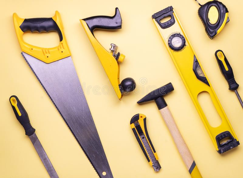 Επίπεδο σχεδιάγραμμα: ένα σύνολο εργαλείων χεριών για την κατασκευή και την επισκευή σε ένα κίτρινο υπόβαθρο στοκ εικόνες