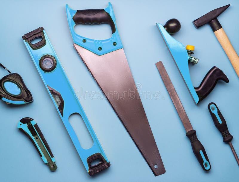 Επίπεδο σχεδιάγραμμα: ένα σύνολο εργαλείων χεριών για την κατασκευή και την επισκευή σε ένα μπλε υπόβαθρο στοκ εικόνες
