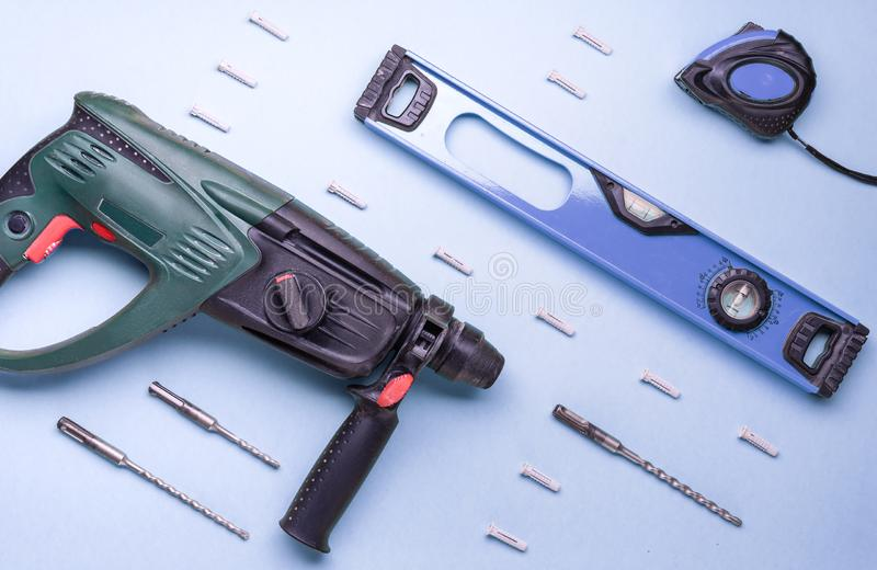 Επίπεδο σχεδιάγραμμα: perforator και άλλα εργαλεία χεριών για την κατασκευή και την επισκευή σε ένα μπλε υπόβαθρο στοκ φωτογραφίες